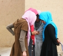Four Afghan girls look at a smart phone.