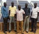 5 men stand in front of a bank of solar panels.
