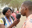 A woman journalist interviews a man at a camp