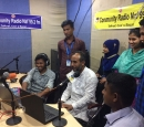 A group of people in a radio studio; some are sitting; some are standing