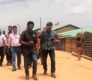 A group of journalists walks along a dirt road in a camp