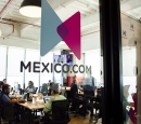 "A group of people sit around tables in a room behind a glass wall that says, ""Mexico.com"""