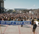 "women stand on a stage with a banner that reads ""Get out of Vietnam"""