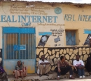 "Some people wait outside a concrete building that says ""Real Internet"""