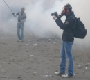 A journalist wearing a gas mask photographs