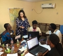 A white woman stands by a table where 4 young Africans are working on computers.
