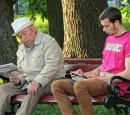 An old man sits on a bench reading a print newspaper; a young man sits next to him looking at a tablet