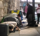 Homeless people are in tents by a brick wall. Two men stand nearby.