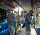 Workers disinfect a subway car