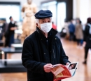 A man wearing a mask stands holding a magazine