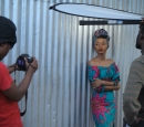 A young woman leans against a metal shed while one man takes photos and another man holds a light