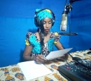A woman sits at a mic in a radio station