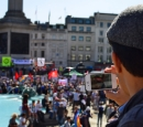 A man videos a protest using his smart phone