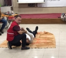 One man lies on a rug while another man demonstrates a safety procedures; others look on