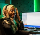 A woman wearing a headscarf and headphones sits in front of a large monitor