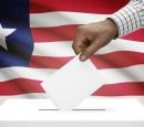 A hand puts a ballot in a box with an American flag as the background