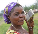 A woman standing outside holds a portable radio up to her ear