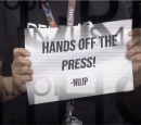 "A protester holds up a sign saying, ""Hands off the Press - NJUP"""