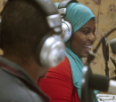 A man and a woman sit in a radio studio