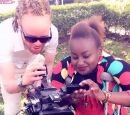 A Black man with albinism and a Black woman using crutches work with a video camera