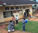 "Four men and a woman stand in front of a concrete building with the name ""Radio Moto"""