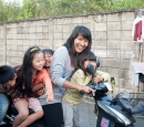 Journalist Ah Mee sits on a motor bike with a group of children around her