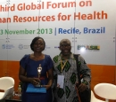 A woman and man sit in front of a sign - Third Global Forum on Human Resources for Health