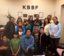 A group of people stand in front of a KBBF sign