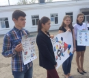 Four young people stand holding posters