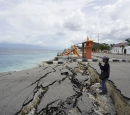 A man stands at the edge of the ocean on a road damaged by the tsunami.