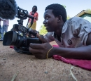 A young man lies on the ground to get a good angle with a video camera