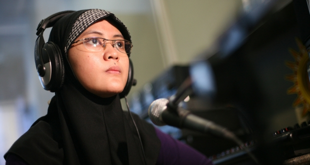 A woman journalist sits at a mic wearing headphones