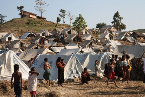 Refugee camp - tents and people walking through the camp.