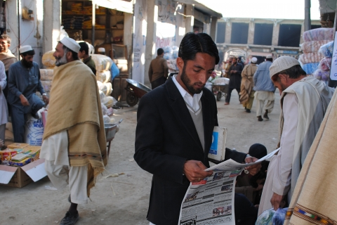A man stands on a busy street reading a newspaper.