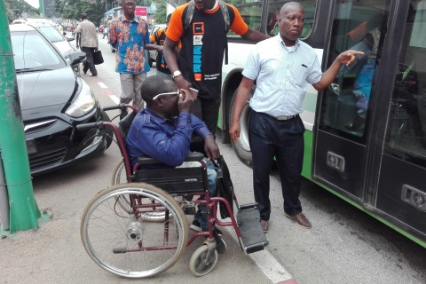 A man using a wheelchair sits outside the door of a bus
