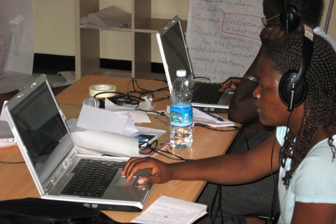 A woman wearing headphones works on a laptop computer