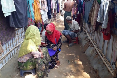 Two women and a man sit in a narrow alley between tents; another man stands