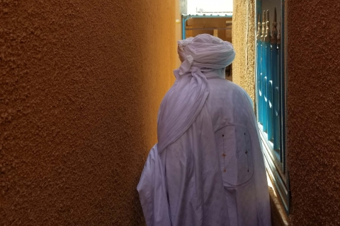A man in a white robe and turban walks between two sandstone buildings.