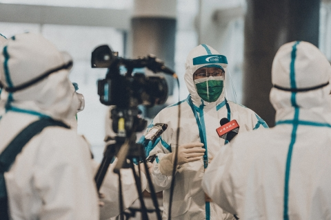 People in full protective gear with a video camera