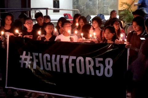 "A group of people holding candles stand behind a banner that says ""#fightfor58"