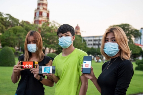 "Three young people, standing outside wearing masks, hold up smart phones that say ""Vote"""