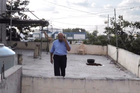 An older man stands on a rooftop deck talking on a phone