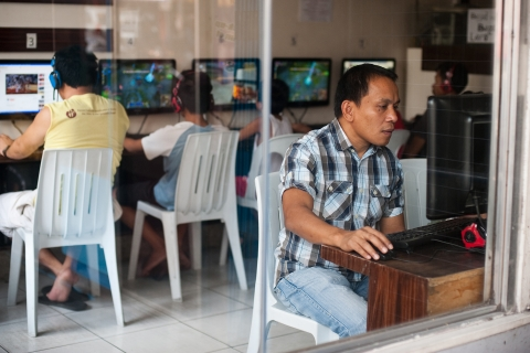 3 people sit at tables in an Internet cafe