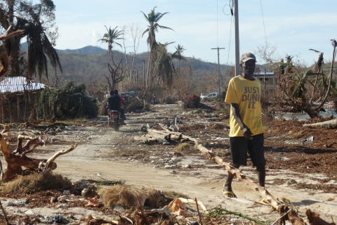 A man walks down a dirt road through an area damaged by the hurricane