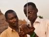 Two men listen to a portable radio