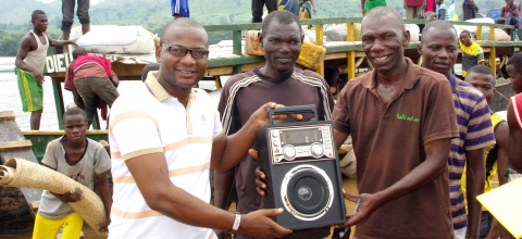 Boatmen on a river in Central African Republic hold sound equipment