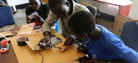 Participants in the peace hack camp solder parts for solar panels