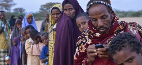 In a line of refugees in Dadaab, Kenya, a man checks his mobile phone.