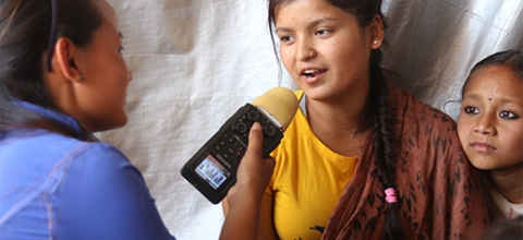 A woman journalist interviews a young Nepalese woman by a tent