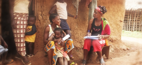 A woman health worker interviews a woman outside her house